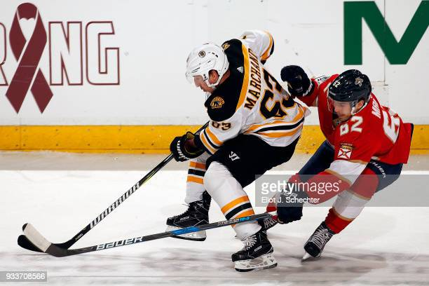 Brad Marchand of the Boston Bruins skates with the puck against Denis Malgin of the Florida Panthers at the BBT Center on March 15 2018 in Sunrise...