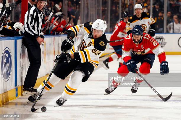 Brad Marchand of the Boston Bruins skates with the puck against Derek MacKenzie of the Florida Panthers at the BBT Center on March 15 2018 in Sunrise...
