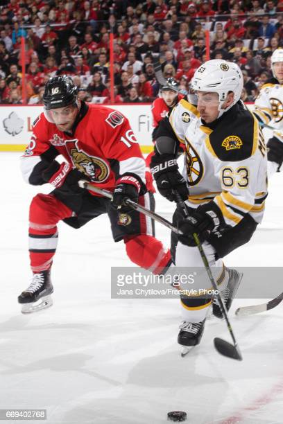 Brad Marchand of the Boston Bruins skates with the puck against Clarke MacArthur of the Ottawa Senators in Game Two of the Eastern Conference First...