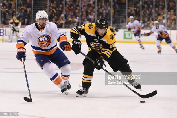 Brad Marchand of the Boston Bruins skates with the puck against Dennis Seidenberg of the New York Islanders at the TD Garden on December 9 2017 in...