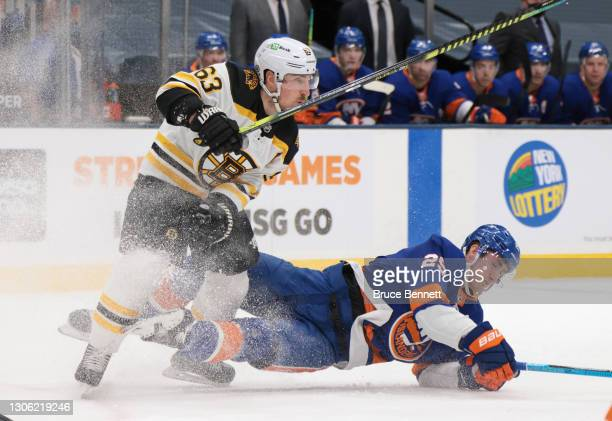 Brad Marchand of the Boston Bruins steps into Brock Nelson of the New York Islanders during the first period at the Nassau Coliseum on March 09, 2021...
