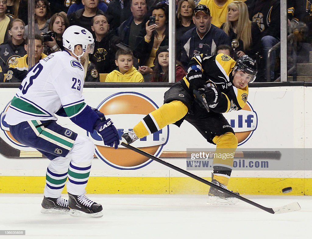 Brad Marchand #63 of the Boston Bruins takes a shot as Alexander Edler #23 of the Vancouver Canucks defends on January 7, 2012 at TD Garden in Boston, Massachusetts.