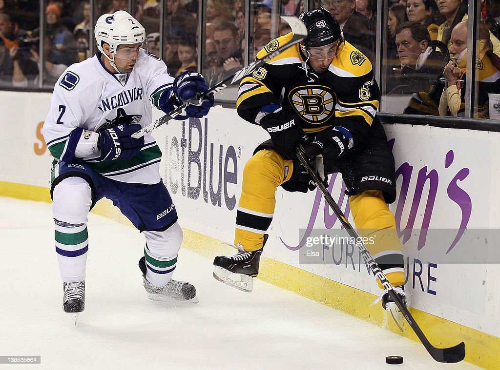Brad Marchand #63 of the Boston Bruins tries to keep the puck as Dan Hamhuis #2 of the Vancouver Canucks defends on January 7, 2012 at TD Garden in Boston, Massachusetts.