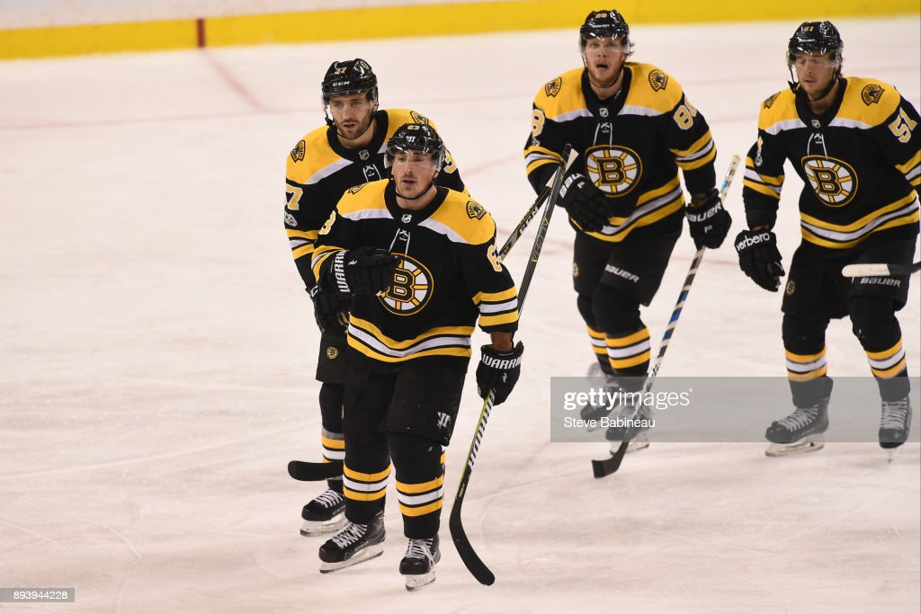Brad Marchand #63, Patrice Bergeron #37, David Pastrnak #88 and Ryan Spooner #51 of the Boston Bruins skate back to the bench to celebrate a third period goal against the New York Rangers at the TD Garden on December 16, 2017 in Boston, Massachusetts.