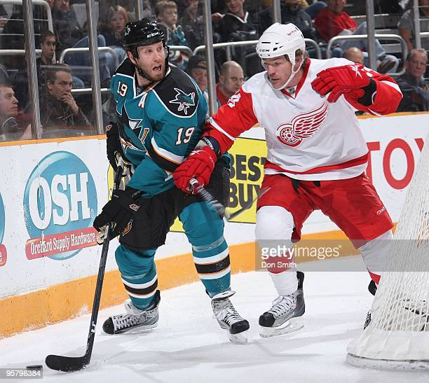 Brad May of the Detroit Red Wings battles behind the net with Joe Thornton of the San Jose Sharks during an NHL game on January 9, 2010 at HP...