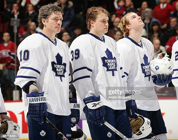 Brad May of the Toronto Maple Leafs stands with his new teammates John Mitchell and Matt Stajan during the singing of the national anthems prior to...