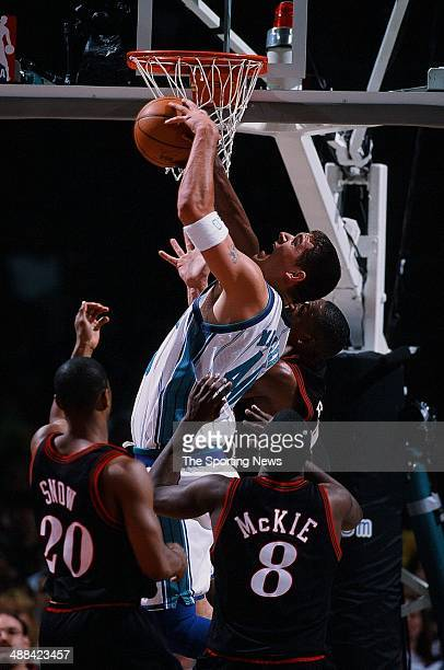 Brad Miller of the Charlotte Hornets goes after a rebound over Eric Snow and Aaron McKie of the Philadelphia 76ers during Game One of the Eastern...