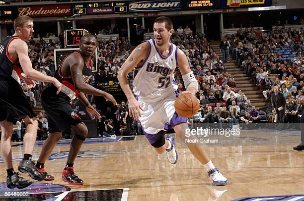 Brad Miller of the Sacramento Kings drives to the basket around Zach Randolph and Steve Blake of the Portland Trailblazers on December 26 2005 at the...