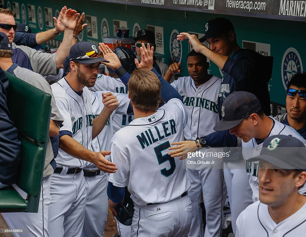 Brad Miller #5 of the Seattle Mariners is congratulated by teammates after scoring on a three-run homer off the bat of Dustin Ackley in the fifth inning against the Washington Nationals at Safeco Field on August 31, 2014 in Seattle, Washington. The Mariners defeated the Nationals 5-3.