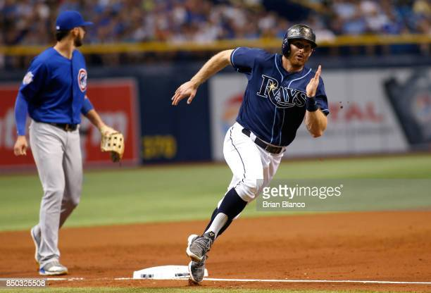 Brad Miller of the Tampa Bay Rays rounds third base in front of third baseman Kris Bryant of the Chicago Cubs on his way to score off of an RBI...