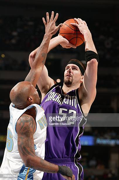 Brad Miller the Sacramento Kings shoots over Anthony Carter of the Denver Nuggets during the game on December 8 2007 at the Pepsi Center in Denver...