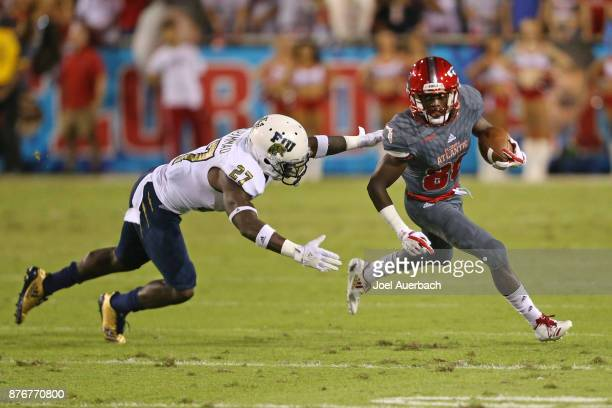 Brad Muhammad of the Florida International Golden Panthers pursues Willie Wright of the Florida Atlantic Owls at FAU Stadium on November 18 2017 in...