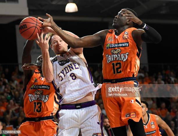 Brad Newley of the Kings contests the ball with Majok Deng and Kouat Noi of the Taipans during the round one NBL match between the Cairns Taipans and...