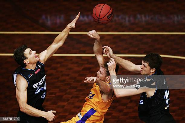Brad Newly of Sydney is fouled by Kirk Penney and Alex Pledger of New Zealand during the round three NBL match between the New Zealand Breakers and...