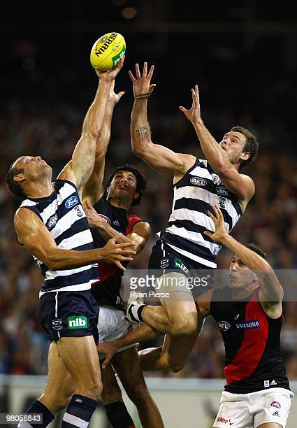 Brad Ottens and Cameron Mooney of the Cats compete for the ball against Patrick Ryder of the Bombers during the round one AFL match between the...