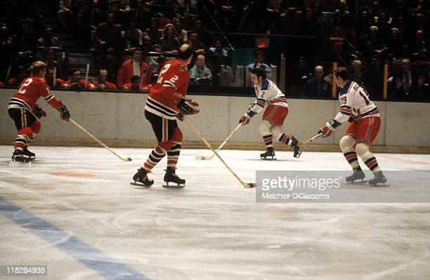 Brad Park and Jean Ratelle of the New York Rangers skate up the ice with the puck as Bill White and Pat Stapleton of the Chicago Blackhawks defend...
