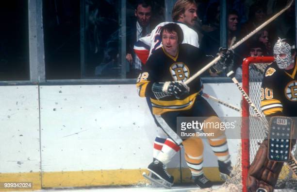 Brad Park of the Boston Bruins checks Bob Nystrom of the New York Islanders as goalie Gerry Cheevers of the Bruins defends the net during an NHL game...