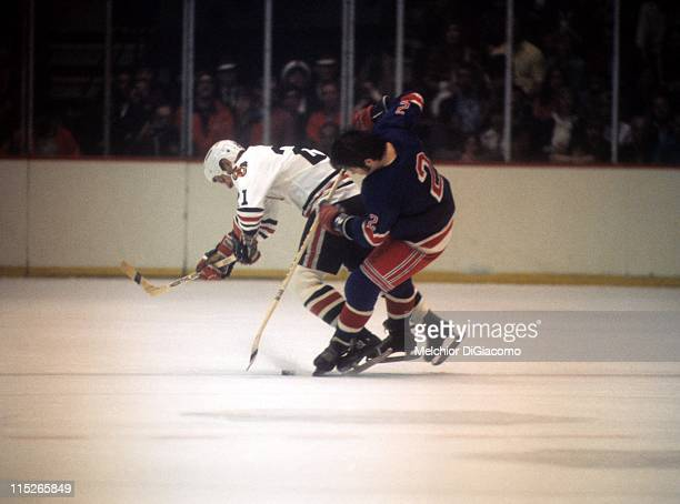 Brad Park of the New York Rangers checks Stan Mikita of the Chicago Blackhawks off the puck during their game circa 1971 at the Chicago Stadium in...