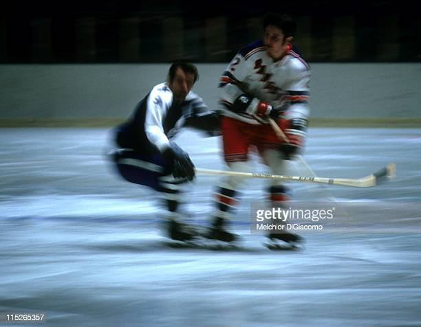 Brad Park of the New York Rangers skates on the ice as Norm Ullman of the Toronto Maple Leafs defends during the Quarter Finals in April 1971 at the...