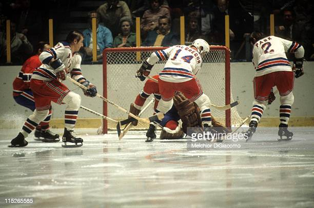 Brad Park Pete Stemkowski and Bruce MacGregor of the New York Rangers look to score on goalie Ken Dryden of the Montreal Canadiens during their game...