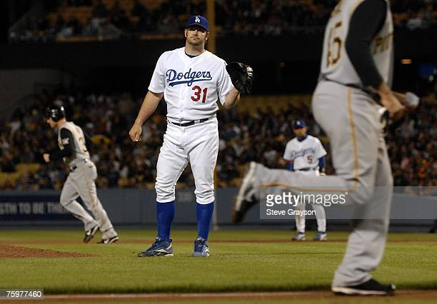 Brad Penny of the Los Angeles Dodgers looks for a new ball after giving up a bases loaded walk to score Ian Snell during their contest against the...
