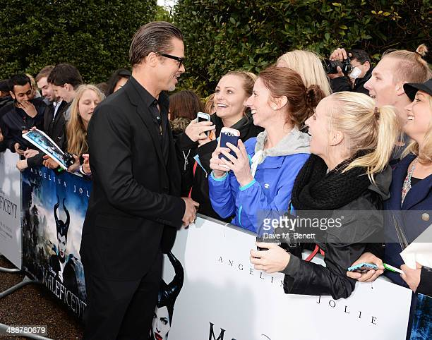 """Brad Pitt signs autographs at a private reception as costumes and props from Disney's """"Maleficent"""" are exhibited in support of Great Ormond Street..."""