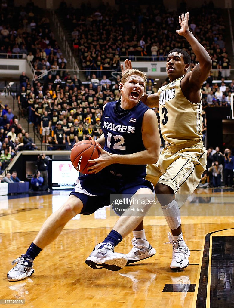 Brad Redford #12 of the Xavier Musketeers dribbles to the hoop as Ronnie Johnson #3 of the Purdue Boilermakers defends at Mackey Arena on December 1, 2012 in West Lafayette, Indiana. Xavier defeated Purdue 63-57.