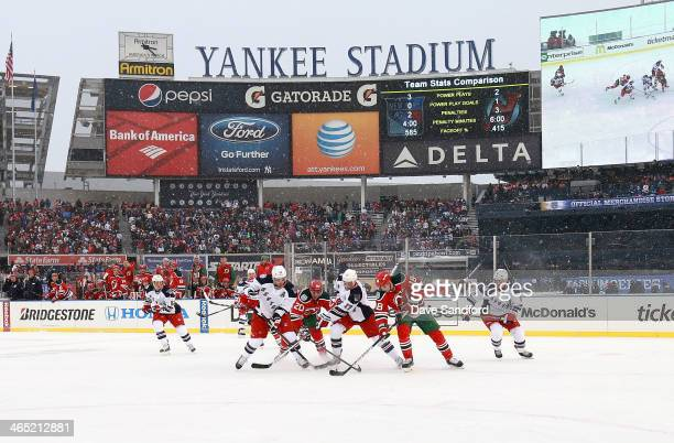 Brad Richards and John Moore of the New York Rangers vie for the puck with Ryan Carter and Steve Bernier of the New Jersey Devils in the high slot...
