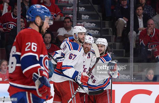 Brad Richards of the New York Rangers celebrates with teammates Benoit Pouliot and Daniel Carcillo after scoring a goal against the Montreal...