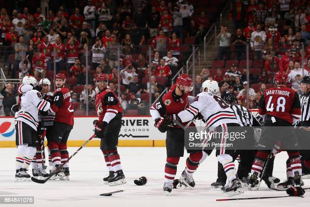 Brad Richardson of the Arizona Coyotes and Jordan Oesterle of the Chicago Blackhawks grab jerseys in a scrum during the third period of the NHL game...