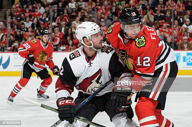 Brad Richardson of the Arizona Coyotes and Tomas Fleischmann of the Chicago Blackhawks get physical in the second period of the NHL game at the...