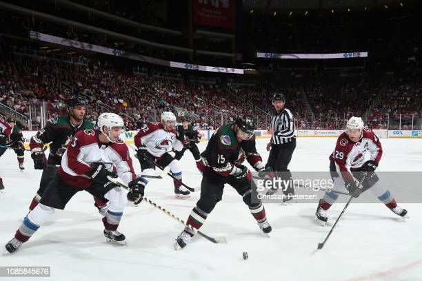 Brad Richardson of the Arizona Coyotes attempts to control the puck inbetween Alexander Kerfoot and Nathan MacKinnon of the Colorado Avalanche during...