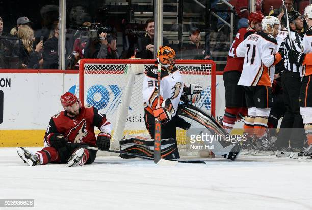 Brad Richardson of the Arizona Coyotes sits on the ice next to goalie Ryan Miller of the Anaheim Ducks as a scuffle breaks out behind the net during...