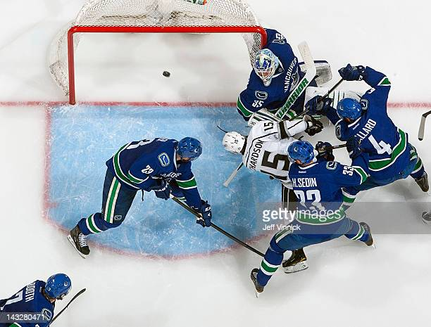 Brad Richardson of the Los Angeles Kings scores the tying goal against Cory Schneider of the Vancouver Canucks despite checking of Alexander Edler,...