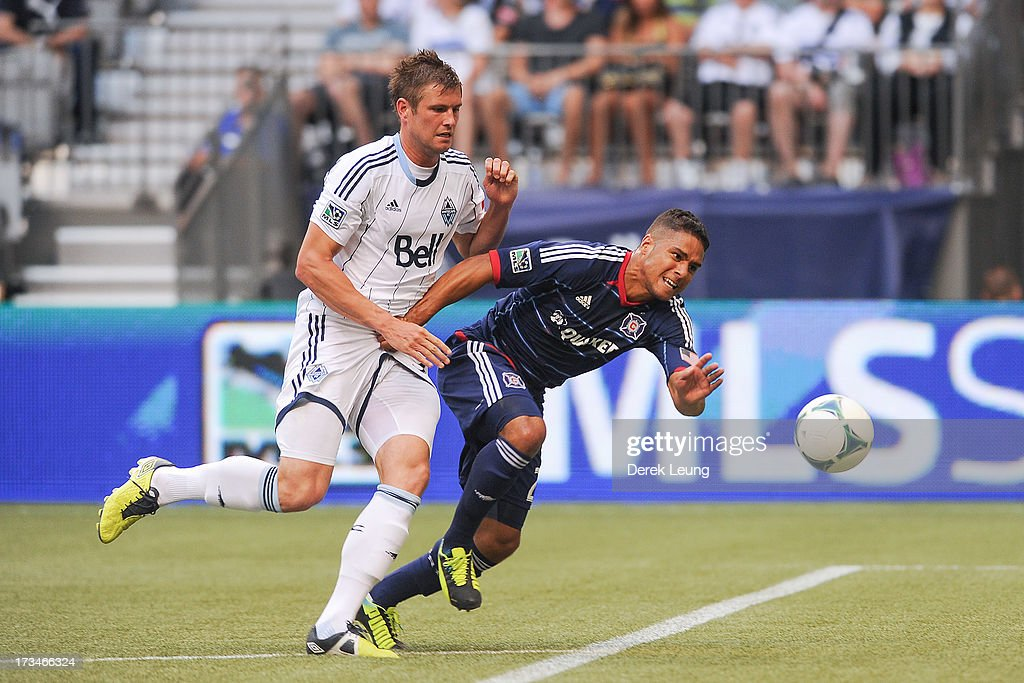 Brad Rusin #3 of the Vancouver Whitecaps battles for the ball against Quincy Amarikwa #24 of Chicago Fire during an MLS Match at B.C. Place on July 14, 2013 in Vancouver, British Columbia, Canada. The Vancouver Whitecaps won 3-1.