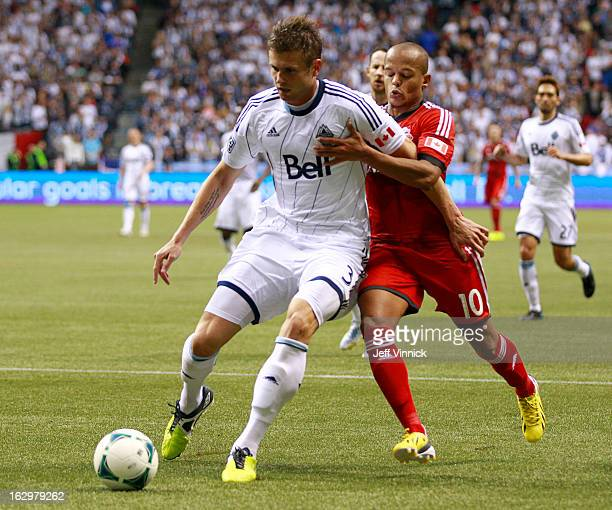 Brad Rusin of the Vancouver Whitecaps FC beats Robert Earnshaw of the Toronto FC to the ball during their MLS game March 2 2013 at BC Place in...