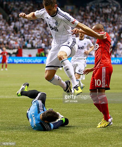 Brad Rusin of the Vancouver Whitecaps FC leaps over goalkeeper Joe Cannon of the Whitecaps while Robert Earnshaw of the Toronto FC watches during...