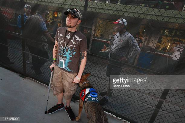 Brad Schwarz with his service dog Panzer attends a Chicago Cubs' game with a group of veterans from the Wounded Warrior Project at Wrigley Field on...