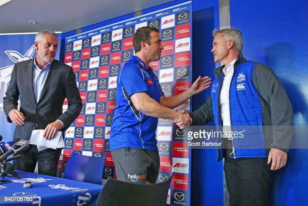 Brad Scott coach of the Kangaroos is congratulated by Kangaroos CEO Managing Director Carl Dilena and Kangaroos Chairman Ben Buckley as he leaves...