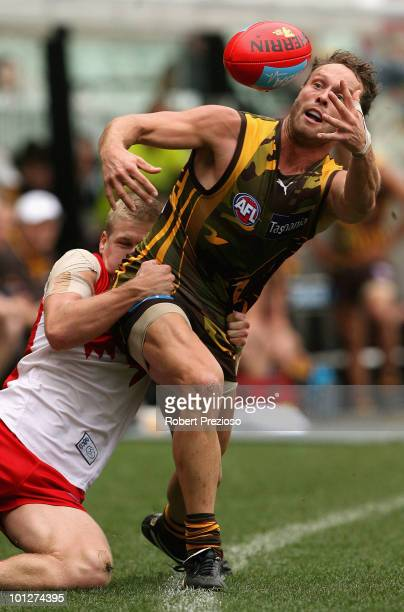 Brad Sewell of the Hawks is tackled by Daniel Hannebery of the Swans during the round ten AFL match between the Hawthorn Hawks and the Sydney Swans...