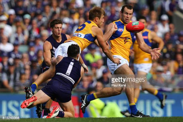 Brad Sheppard of the Eagles handballs under pressure from Hayden Ballantyne of the Dockers during the round 17 AFL match between the Fremantle...
