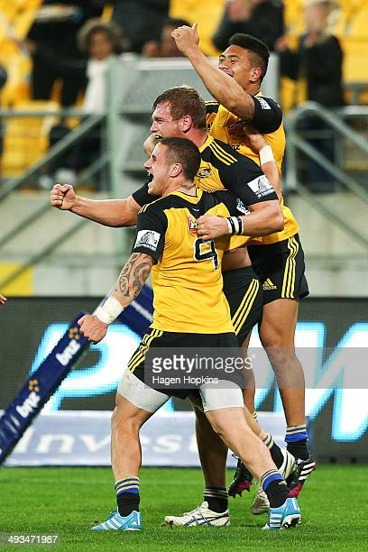 Brad Shields of the Hurricanes celebrates his try with teammates TJ Perenara and Ardie Savea during the round 15 Super Rugby match between the...