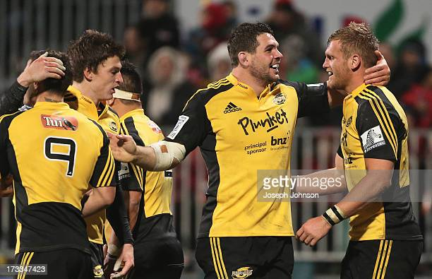 Brad Shields of the Hurricanes celebrates with Ben May and TJ Perenara and Beauden Barrett after scoreing a try during the round 20 Super Rugby match...