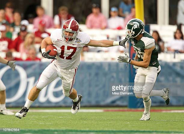 Brad Smelley of the Alabama Crimson Tide runs after a catch stiffarming Josh Bodell of the Michigan State Spartans during the Capitol One Bowl at the...