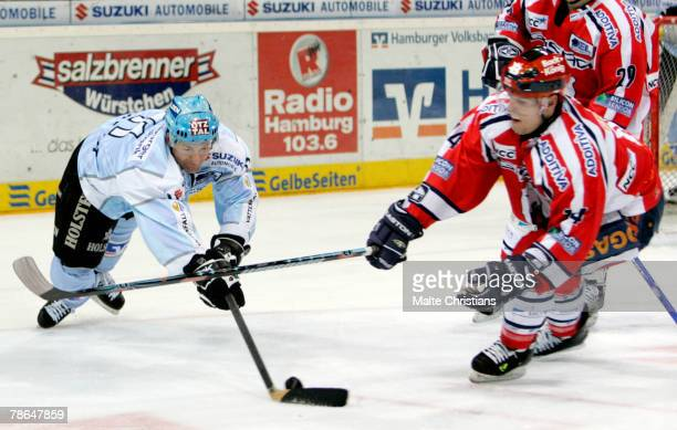 Brad Smith of Hamburg competes with Andre Renkel of Berlin during the DEL match between Hamburg Freezers and Eisbaeren Berlin at the Color Line Arena...