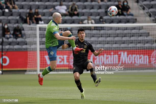 Brad Smith of Seattle Sounders and Mohamed Traore of Los Angeles FC battle for the ball during the first half at Banc of California Stadium on April...