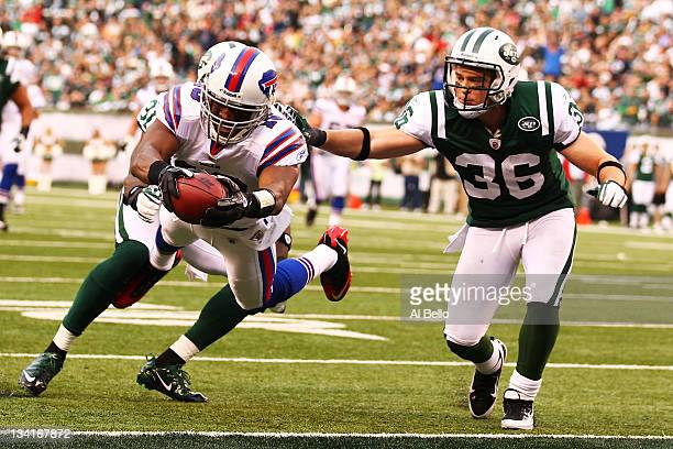 Brad Smith of the Buffalo Bills scores a touchdown as Antonio Cromartie and Jim Leonhard of the New York Jets cannot make the tackle during their...