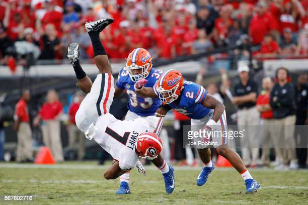 Brad Stewart of the Florida Gators upends D'Andre Swift of the Georgia Bulldogs after a catch in the fourth quarter of a game at EverBank Field on...