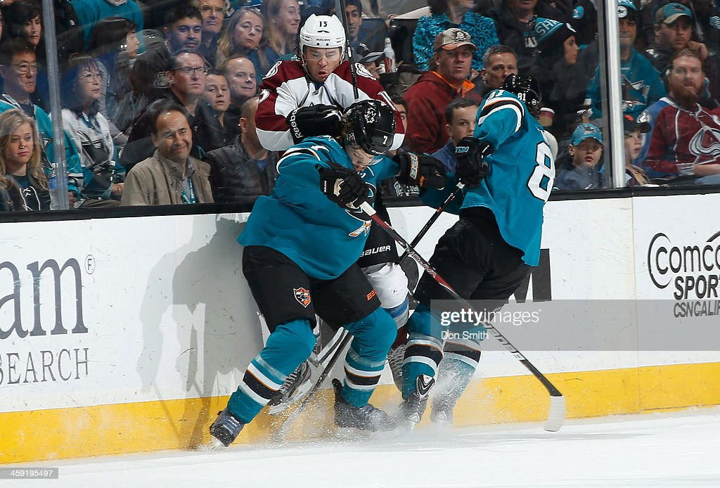 Brad Stuart #7 and Tyler Kennedy #81 of the San Jose Sharks get physical against PA Parenteau #15 of the Colorado Avalanche during an NHL game on December 23, 2013 at SAP Center in San Jose, California.