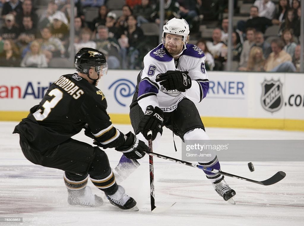 Brad Stuart # 6 of the Los Angeles Kings has the puck poked away by Stephane Robidas #3 of the Dallas Stars at the American Airlines Center on October 10, 2007 in Dallas, Texas .